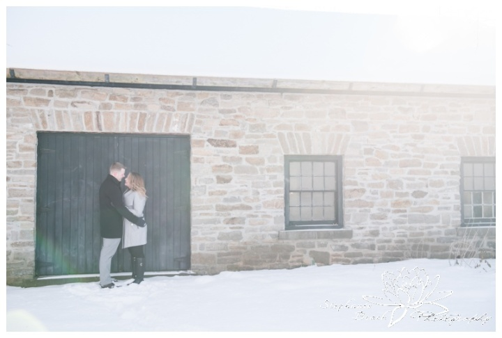 Merrickville-Winter-Engagement-Session-Stephanie-Beach-Photography-Christmas-portrait-stone-building-ruins-sunflare